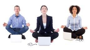 Los hombres de negocios jovenes que se sientan en yoga presentan con los ordenadores portátiles aislados fotografía de archivo libre de regalías