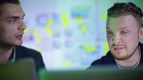 Los hombres de negocios jovenes trabajan incluso en la noche almacen de video