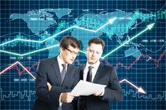 Los hombres de negocios miran en el papel el fondo de los gráficos de negocio Fotografía de archivo