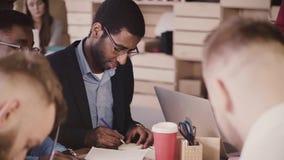 Los hombres de negocios multiétnicos se inspiran juntos en la reunión de la oficina, escriben en los papeles de nota pegajosos en almacen de metraje de vídeo