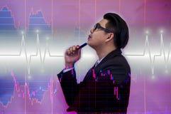 Los hombres de negocios puestos en un traje negro, sostienen una pluma, mirando la carta común, concepto del riesgo de inversión imagen de archivo