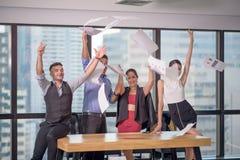 Los hombres de negocios que celebran lanzando sus documentos comerciales y documentos vuelan en el aire, poder de la cooperaci?n, imagen de archivo