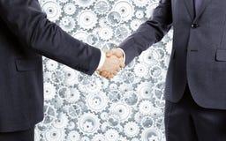 Los hombres de negocios sacuden las manos en el fondo de las ruedas dentadas Imagen de archivo libre de regalías