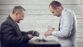 Los hombres de negocios se divierten que comparte el dinero almacen de metraje de vídeo