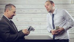 Los hombres de negocios se divierten que comparte el dinero almacen de video