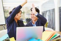 Los hombres de negocios se felicitan con el alto cinco imagenes de archivo