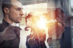 Los hombres de negocios se unen a pedazos del rompecabezas Concepto de trabajo en equipo y de sociedad Exposición doble fotos de archivo