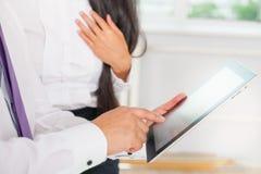 Los hombres de negocios se vistieron en blanco usando la PC de la tableta en la oficina Imágenes de archivo libres de regalías