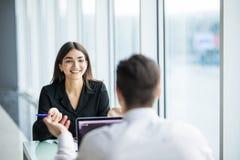 Los hombres de negocios sirven y mujer que tiene reunión en la tabla en oficina moderna contra ventanas panorámicas Foco en mujer foto de archivo