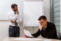 Los hombres de negocios solucionan un problema Imagenes de archivo