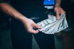 Los hombres de negocios sostienen muchos billetes de banco, colocando a hombres de negocios acertados fotografía de archivo libre de regalías