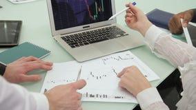 Los hombres de negocios y la empresaria discuten la situación financiera actual en la oficina almacen de video