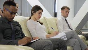 Los hombres de negocios y la empresaria de Tho toman las notas que se sientan en la conferencia en oficina brillante moderna almacen de metraje de vídeo