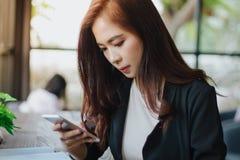 Los hombres de negocios y las mujeres están utilizando el móvil y el teléfono elegante del tacto para fotografía de archivo