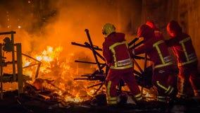 Los hombres del fuego empujan restos de un falla en el fuego durante Las Fallas en Valencia Spain fotografía de archivo