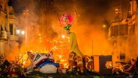 Los hombres del fuego empujan una escultura en el fuego durante Las Fallas en Valencia Spain foto de archivo