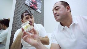 Los hombres del Orthodontist y del dentista discuten plan del tratamiento con el modelo del mand?bula almacen de metraje de vídeo