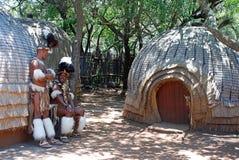 Los hombres del Zulú que llevan al guerrero se visten cerca de la casa tribal de la paja, Suráfrica Foto de archivo libre de regalías