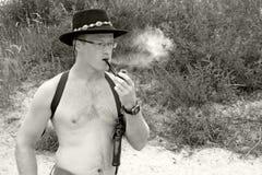 Los hombres descamisados fuman un tubo Imagen de archivo