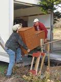 Los hombres descargan una furgoneta móvil imagenes de archivo