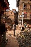 Los hombres despejan los escombros en terremoto golpearon Bhaktapur, Nepal Foto de archivo libre de regalías