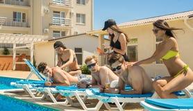 Los hombres disfrutan de un masaje de mujeres cerca de la piscina Fotos de archivo libres de regalías