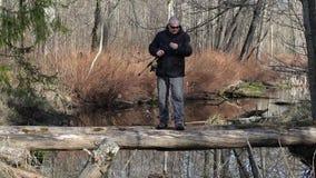 Los hombres elaboran la caña de pescar en registro que cruzan el río almacen de video
