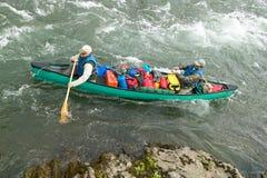 Los hombres en aventura canoe en rápidos de Alaska del río Foto de archivo