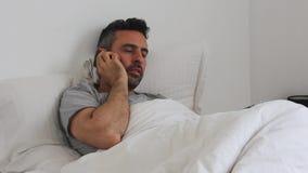 Los hombres en cama utilizan su smartphone almacen de metraje de vídeo