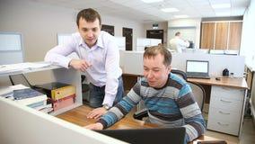 Los hombres en la oficina discuten los problemas del trabajo que se colocan delante del ordenador metrajes