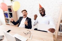 Los hombres en trajes de negocios se están sentando en una oficina brillante en casquillos festivos el 1 de abril Fotos de archivo