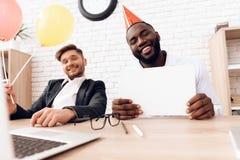 Los hombres en trajes de negocios se están sentando en una oficina brillante en casquillos festivos el 1 de abril Fotos de archivo libres de regalías
