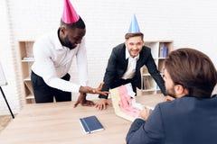 Los hombres en trajes de negocios y sombreros festivos pegaron un cuaderno de su colega con las etiquetas engomadas Fotografía de archivo libre de regalías