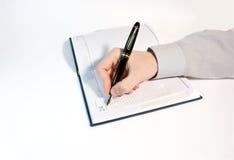 los hombres escriben en agenda Imagen de archivo libre de regalías