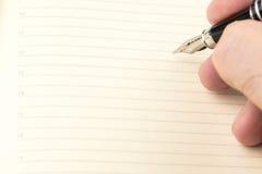 Los hombres están escribiendo con la pluma de la tinta en el cuaderno en blanco con las líneas Imagen de archivo