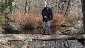 Los hombres están pescando en registro que cruzan el río metrajes