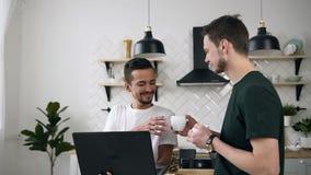 Los hombres gay de los pares caucásicos atractivos están bebiendo el café y están trabajando en cocina del ordenador portátil en  almacen de video