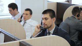 Los hombres hablan en el teléfono, trabajando en centro de atención telefónica almacen de metraje de vídeo