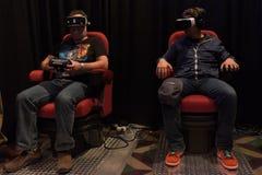 Los hombres intentan las auriculares del engranaje VR de Samsung de la realidad virtual Imagen de archivo