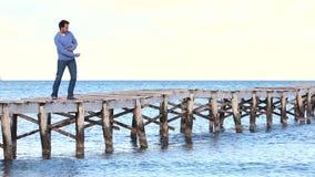 Los hombres jovenes absorbieron en piedras que lanzaban del pensamiento en el agua metrajes
