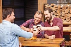 Los hombres jovenes alegres están descansando en cervecería Foto de archivo