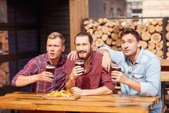 Los hombres jovenes alegres están mirando el juego en pub Fotos de archivo