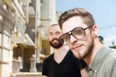 Los hombres jovenes atractivos están caminando a través de ciudad Fotos de archivo libres de regalías