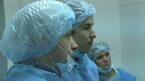 Los hombres jovenes de la vista lateral del primer en trajes estéril escuchan la conferencia almacen de video