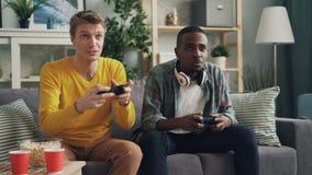 Los hombres jovenes felices están jugando al videojuego con la consola usando hogar del st de las palancas de mando Los individuo metrajes