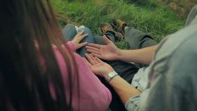 Los hombres jovenes guardan la mano de la mujer en un verde del fondo almacen de metraje de vídeo