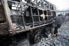 Los hombres jovenes miran el auto militar del quemar en las barricadas de la ciudad de ocupación de la nieve durante alboroto imágenes de archivo libres de regalías