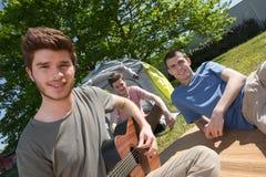 Los hombres jovenes se sentaron fuera de la tienda que tocaba la guitarra Fotografía de archivo libre de regalías