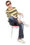 Los hombres jovenes se sientan en cruz de la silla las piernas Imágenes de archivo libres de regalías