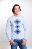 Los hombres jovenes se vistieron en un suéter y pantalones vaqueros fotografía de archivo